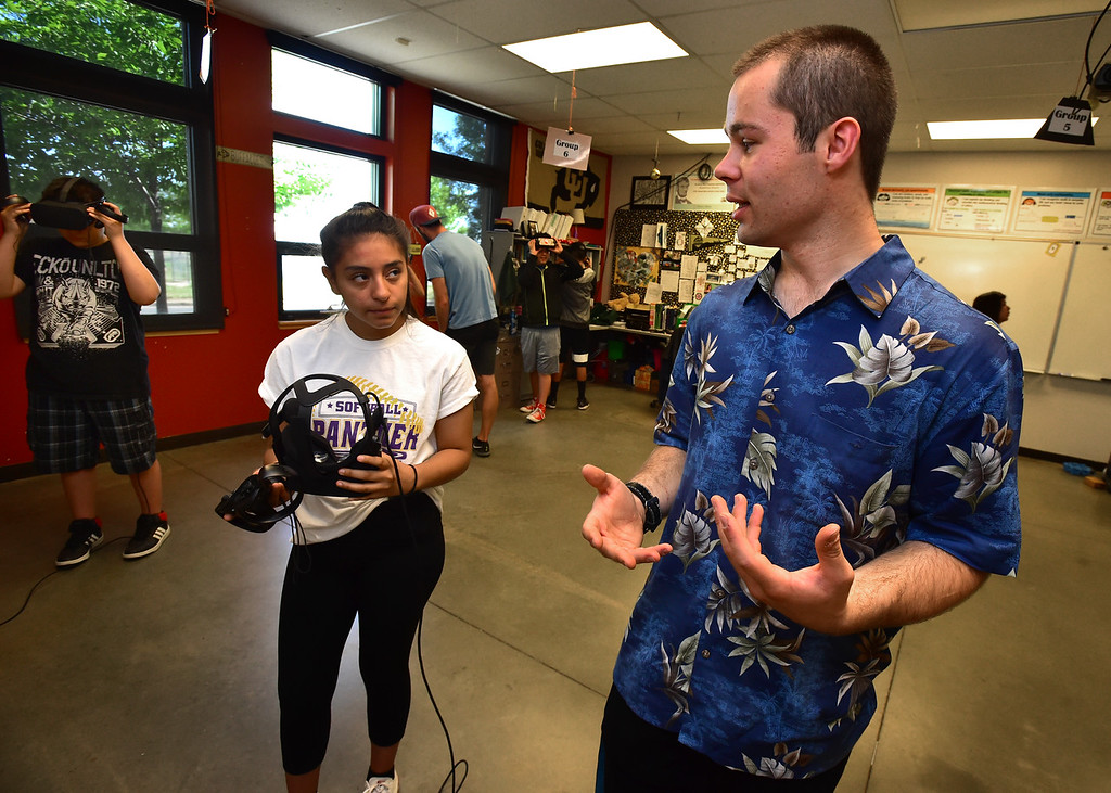 . Ryan Zech of the Reality Garage explains a virtual reality system to Jenny Rocha during the I Have A Dream summer STEM conference at Peak to Peak Charter School in Lafayette on Thursday.  For more photos go to dailycamera.com Paul Aiken Staff Photographer June 7, 2018