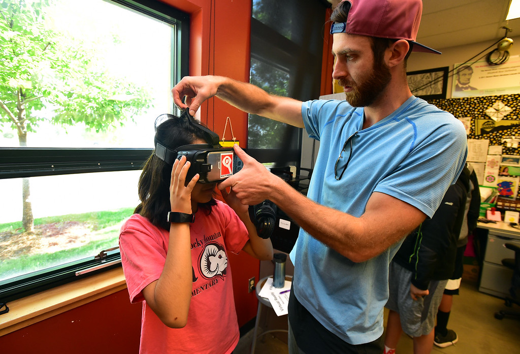 . Jamie Eggleston of the Reality Garage fits a virtual reality system on Grecia Torres during the I Have A Dream summer STEM conference at Peak to Peak Charter School in Lafayette on Thursday.  For more photos go to dailycamera.com Paul Aiken Staff Photographer June 7, 2018