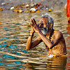 A man saluting the sun god and taking a ritual dip in the Ganga at Varanasi