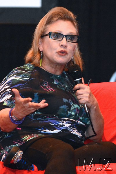 Star Wars actress and best-selling author Carrie Fisher settles in to a sofa on stage with her pet dog for a Q&A at FandomFest 2015 in the KY International Convention Center on Saturday, August 8, 2015.