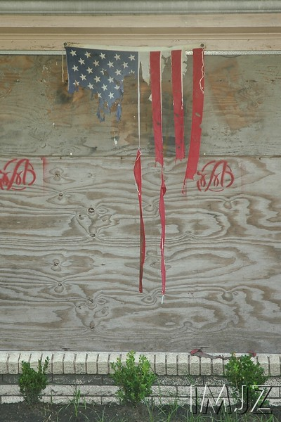 A worn and tethered American flag remains draped over the boarded window of a New Orleans home, still unoccupied two years after Hurricane Katrina. July 18, 2007.