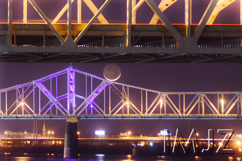 The crescent moon sits between the Kennedy and Clark bridges over the Ohio River.