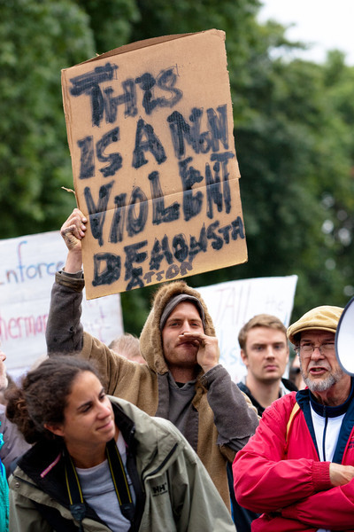 "A protester at the Occupy Portland gathering holds up a sign reading, ""This is a non-violent demonstration""."