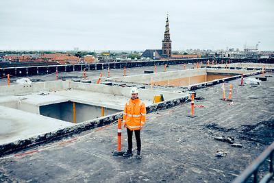 Rune Holm Madsen, Produktionsdirektør - Tscherning (fotograferet ved Strandgade 7 i København.)  Historien handler om, at der af hensyn til klimaet skal bygges bæredygtigt. Det er dog endnu lidt småt med materialer, der ikke er så miljøbelastende, som de gængse. Men det er 70 firmaer dog gået sammen om at gøre noget ved.  En del er vistnok stadig gode hensigter. Men min case - nedrivningsfirmaet Tscherning - kan fortælle om, at man allerede er begyndt at skille huse mere forsigtigt ad i stedet for bare at sætte en bulldozer på dem. Taler først med dem i morgen - men noget af Botanisk Have-huset genbruges vist af Årstiderne!?  Mange materialer kan faktisk genbruges, så affald pludselig bliver en ressource. Og det betyder, at hvor nedriverne traditionelt har betalt for at slippe af med murbrokker etc. - så kan de i dag ligefrem få penge for skramlet...  Det her er selvfølgelig kun en begyndelse! De fremsynede i branchen vil gerne have, at tingene bliver sat meget mere i system, så producenterne af beton, mursten etc. kan tilbyde standardiserede, certificerede og bæredygtige byggematerialer. Sagt på en anden måde skal det her op i stor skala for at batte noget og være økonomisk attraktivt.  Og det er bl.a. det, de 70 firmaer vil arbejde for - ligesom Dansk Standard arbejder for en fælleseuropæisk mærkning (eller noget i den retning.)  Her kunne Danmark måske - fordi vi allerede er begyndt at tænke og handle i de baner - få en slags first mover-fordel.  Mange ord, men på den måde fik jeg også lige tingene vendt rigtigt i mit eget hoved ;-)  Casen - som meget gerne må blive fotograferet allerførst på dagen mandag, så vi kan have billederne senere mandag - er:   ===================  BØRSEN