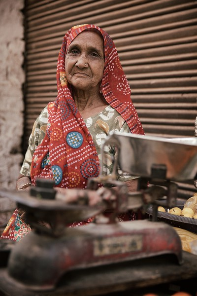 "Kasturi, 74, Delhi, India.<br /> <br /> I was instantly drawn to Kasturi. Both her face and eyes told so much, yet it was her words that affected me the most, as she acknowledged that now, only death awaits her …<br /> <br /> Kasturi is a mother to three girls and two boys, although one of her sons passed away thirty years ago. She still looks after her remaining son who is deaf and dumb, a job that is very difficult but what else can she do? Kasturi explained she is aided by local boys who are like family to her. When I asked her about her own two Grandchildren, she said she could not say or do anything, but simply hopes they turn out to be good people.<br /> <br /> Kasturi mentioned that many tourists ask to take her photo as she sells fruit and veg on the street corner and she's always obliging as it makes them happy. When I asked her about own happiness and inspiration though, she said she is too old. She has seen everything and there is just death now. God has given her life and she has lived it.<br /> <br /> ""I've only done good. I've never abused or sworn at anyone"".<br /> <br /> 2015."