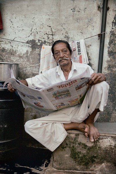 "Muhammad Bhai, 70, Mumbai, India.<br /> <br /> ""I prefer to get my news from the paper, I don't like modern technology"". <br /> <br /> Muhammad Bhai seemed like a Dharavi fixture, as relaxed with his paper. His favourite pastime is reading world news and he's grateful that his vision still permits him to do so. <br /> <br /> As he sat outside his house, I noted Muhammad Bhai appeared to be very content:<br /> <br /> ""I like it here. I've lived here all my life. I know everyone and it's like a village. The only thing that has changed is it's got busier"".<br /> <br /> 2015."