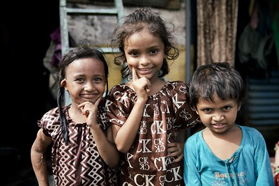 Najameen, 6 & Sajiya, 7, with their younger brother, Mumbai, India.  Najameen and Sajiya shared a connection that was very touching. The two sisters were such an amazing expression of happiness and joy in life. They posed for the camera and danced around, laughing uncontrollably, as their brother did his best to join in.  From my point of view I wanted to know more about their story. I tried in vain to talk to Najameen and Sajiya but they didn't want to stop having fun - I couldn't blame them! Life in this area of Mumbai is very, very tough, but all I could see were these shining faces that made me smile contagiously!  2015.  *A Special thanks to my fixer and translator, Dinesh Dubey, for making my photos and stories in Mumbai possible.