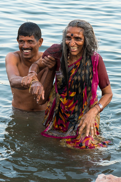 Son assists with sacred immersion in the Ganges