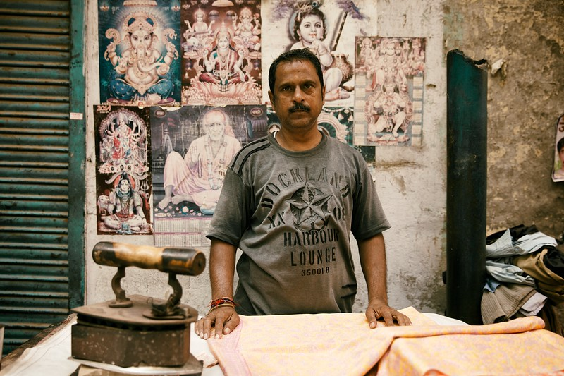 "Raju, 45, Delhi, India. <br /> <br /> ""My wrist and arm get so sore, the only way I can sleep is if I hold my arm above my head"".<br /> <br /> I met Raju on my first visit to Delhi in 2014 and surprisingly he remembered me a year later. Nothing seemed to have changed. His shop hadn't moved and he was still using his incredibly heavy coal-filled iron, just like he'd done for the last 25 years. He told me his shop has been here the longest but now there is much more competition than before. <br /> <br /> ""I have good children"".<br /> <br /> When I bumped into Raju on my return visit, he had one of his grandchildren in his arms and was  looking very happy and relaxed. I then realised that his reserved and stern demeanour quickly vanishes once you get to know him. Raju told me he had 3 grandchildren and 3 children and appeared most proud when he explained that his kids all worked in IT.<br /> <br /> ""There was an Australian here shooting money everywhere … it was crazy!!!""<br /> <br /> When I told him I was from Australia his eyes lit up. He told me that one time a rich Australian came here and shot money out of a gun. People were scampering in all directions trying to cash in. It sounded to me like a scene from a movie and seemed a far cry from the 7 cents Raju is paid for each item he irons. <br /> <br /> On a side note, Raju is the brother-in-law of Pappan (who also features on my website). Both were adorable people and I'm very grateful for the time we spent together.  <br /> <br /> 2015."
