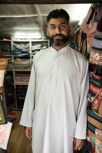 "Amin, McLeod Ganj, India. <br /> <br /> ""I originally made carpets"". <br /> <br /> Amin taught himself to make jewellery by simply observing. He now runs his own store as well as teaching others his craft. <br /> .<br /> ""I miss home, but I do like it here"". <br /> <br /> Each year, Amin travels to McLeod Ganj from Kashmir to set up shop on a busy tourist street. He leaves behind his home and family in the mountains for months on end.<br /> <br /> Amin in has two children and around a dozen grandchildren (he thinks). When I asked him what hopes he has for his grandchildren, he asked me what do I think is good. I said that a lot of people say the most important thing is that they turn out to be good people. He agreed.<br /> <br /> On a side note Amin's English was amazing. He is self taught and possesses an incredible vocabulary. Amin seems to be very talented at the things he sets his mind to.<br /> <br /> 2015."