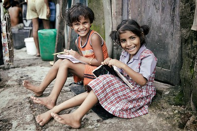 Archana, 6 & Anjali, 6, Mumbai, India.  Many shanties align the narrow docks in the ship wrecking yards in central Mumbai. It was outside one of these homes that I stumbled upon two girls writing the English alphabet for homework.  The first thing that surprised me was that both Archana and Anjali had the opportunity to learn English at school. I had a preconception that not all children in India could readily access education, but the more I saw throughout the country, the more I realised this assumption was wrong. My second reason for being surprised was that they were both so happy and eager to learn. I look back to myself as a six year old and there was no way I was going to do any homework!  It is heartening to see India as a whole, placing so much importance on education. Both Anjali and Archana said they would like to be teachers when they grow up. I would love to know what their futures hold …  2015.
