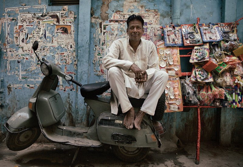 "Muhammad Kale, 40, Delhi, India. <br /> <br /> ""I also play drums at weddings"".<br /> <br /> Muhammad Kale has spent all his life in Paharganj and knows everyone in the area. He sells children's toys for 2 rupees each as he relaxes back on his scooter. ""It's good living here"". <br /> <br /> 2015."