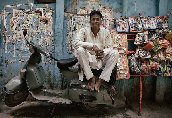 "Muhammad Kale, 40, Delhi, India.   ""I also play drums at weddings"".  Muhammad Kale has spent all his life in Paharganj and knows everyone in the area. He sells children's toys for 2 rupees each as he relaxes back on his scooter. ""It's good living here"".   2015."