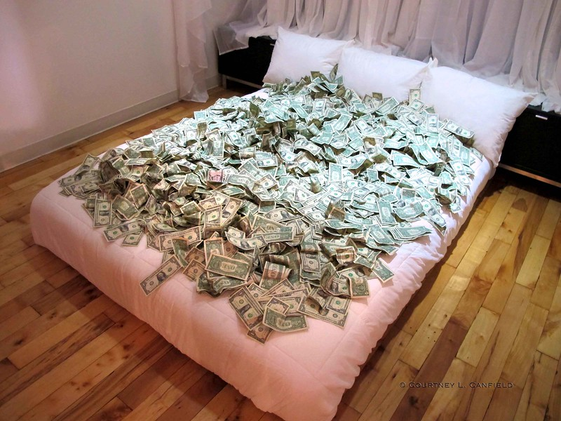 """Rolling in Filth"" <br /> Interactive Art Installation by Caridad Sola<br /> $10,000 on a Queen Size Bed"