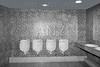 Bathroom urinal in a row with gray tiles