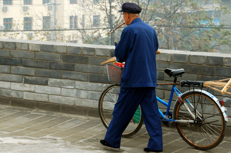street scenes, China man with a bike, shoppig, not the cigarette holder