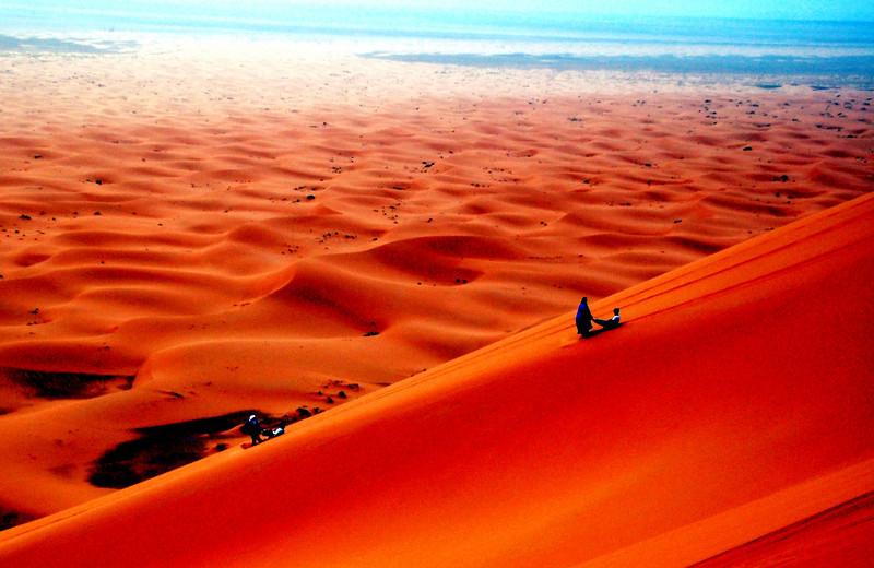"""doing the """"berber slide"""" down the dunes """"erg chebbi"""" in the Saraha desert, Morocco."""