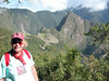 at the sun gate over machu piccu  in the background behind her left shoulder. UNESCO WORLD HERITAGE SITE