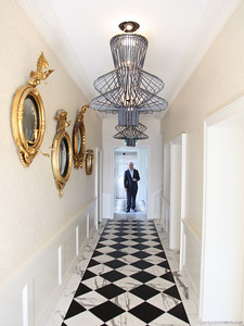 the entrance hallway features contemporary chandeliers and old mirrors