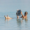 Man reading newspaper while swimming in Dead Sea, Israel