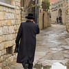 Rear view of man walking in wet street, Safed, Northern District, Israel