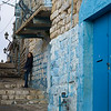 Woman leaning on stone wall in street, Safed, Northern District, Israel