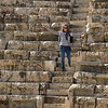 Happy woman standing on stone steps at Roman amphitheater, Bet She'an National Park, Haifa District, Israel