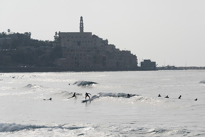 Tourists surfing in the beach with city in the background, Tel Aviv-Yafo, Tel Aviv, Israel