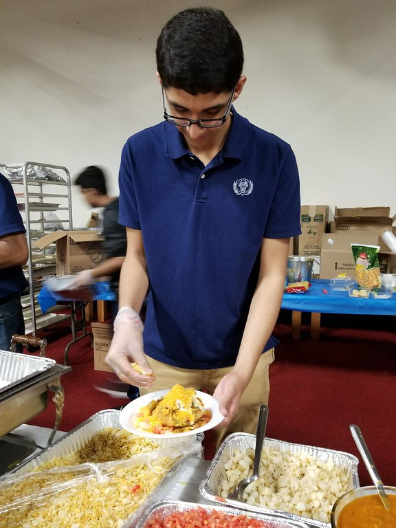 . High school volunteers helping to serve the menu provided. Here is Davis Patel of ISSO Youth Group.
