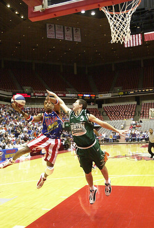 Josh Hale/Iowa State Daily<br /> Curley Johnson of the Harlem Globetrotters tries to shoot around a player from the New York Nationals duing the Globetrotters game in Hilton on Tuesday evening.  (1-09-01)