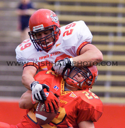 Josh Hale/Iowa State Daily<br /> Jordan Wagner tries to get the ball out of Ryan Sloth's hands during the second half of the spring football game on Saturday afternoon.  (4-22-00)
