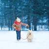 Christmas, winter and people concept - happy teenager boy running and playing with white Samoyed dog outdoors in the park on a winter day