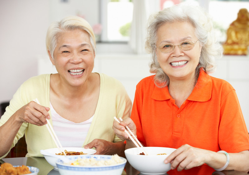 Two Senior Chinese Women Sitting At Home Eating Meal