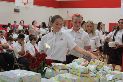 IWA seventh graders Lucy Kainer (left), Lillian Smith (center), and Kya Wight (right) place gifts of baby items in front of the statue of Mary.