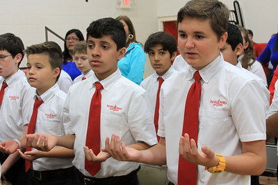 IWA sixth graders Maximillien Harrison (left), Stephen Sauceda (center), and Stephen Canterbury (right) recite the Our Father prayer during a school Mass on May 19.