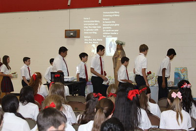 IWA Middle Level students present gifts at the foot of the statue of Mary with  during a school Mass in honor of Mary.