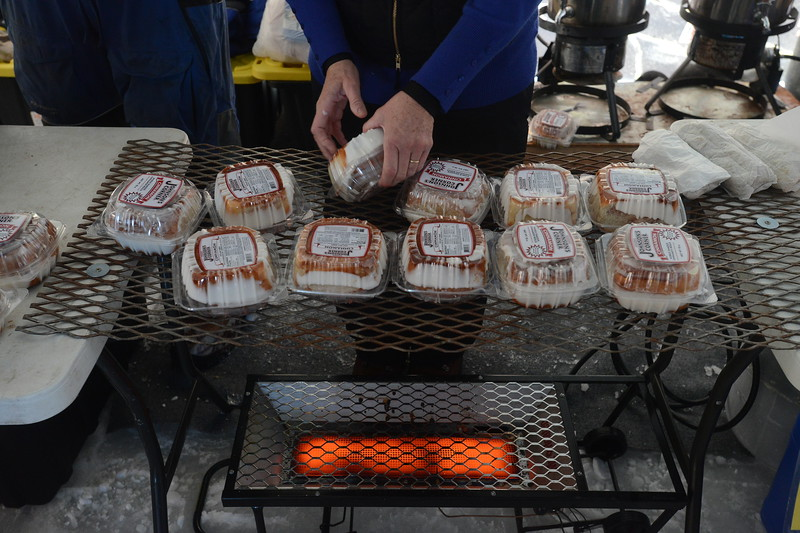Volunteer Diane Dykstra keeps Johnson's Corner cinnamon rolls warm over a propane heater in the warming tent during the Ice Addiction fishing tournament Saturday, Jan. 7, 2017, at Boyd Lake State Park in Loveland.  (Photo by Craig Young / Loveland Reporter-Herald)