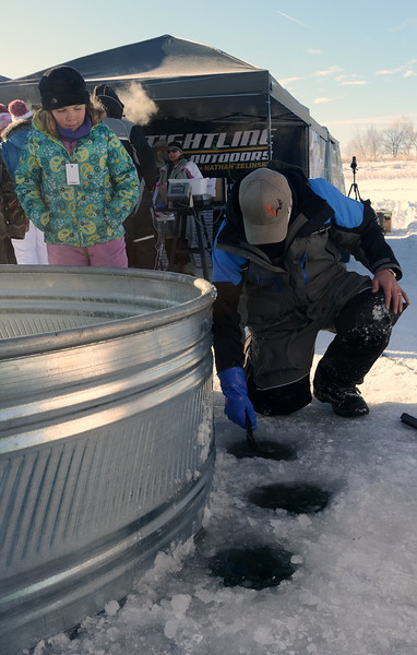 Kat Reger, 10, of Fort Collins, watches as Tightline Outdoors employee John Bruckner returns a trout to the water during the Ice Addiction fishing tournament Saturday, Jan. 7, 2017, at Loveland's Boyd Lake State Park.  (Photo by Craig Young / Loveland Reporter-Herald)