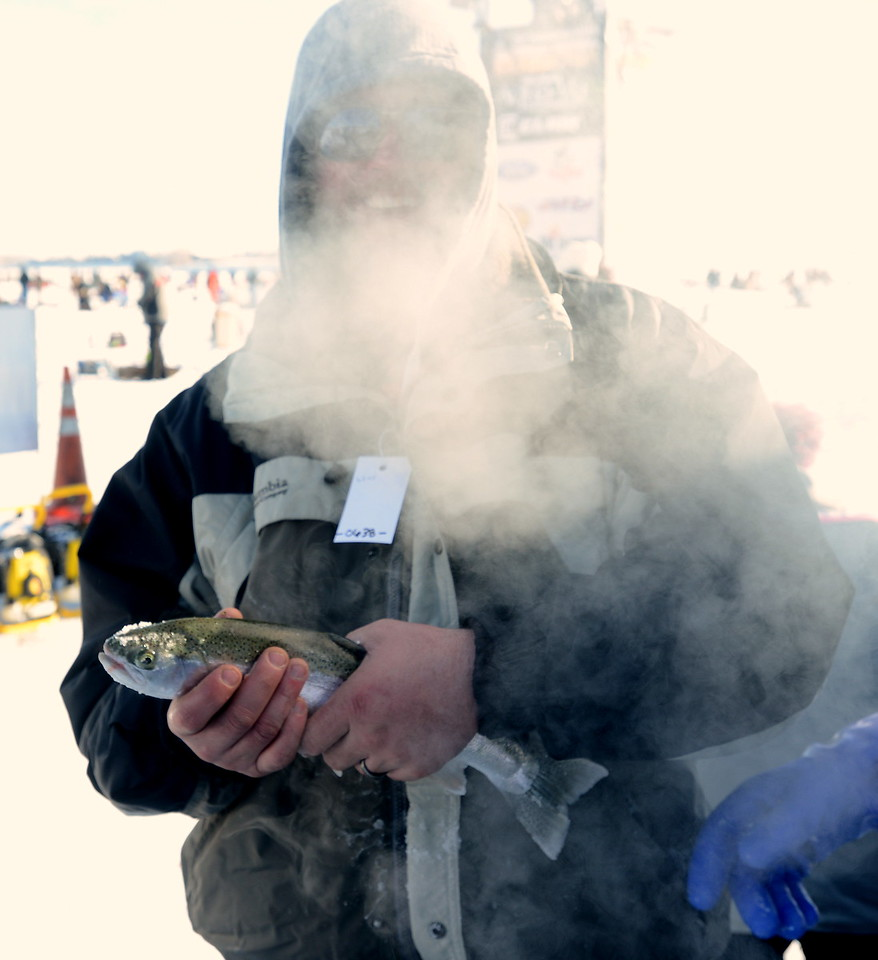 Almost obscured by the vapor from his breath on a below-zero morning, Wellington resident Ricky Lee shows off his 1.24-pound trout during the Ice Addiction fishing tournament Saturday, Jan. 7, 2017, at Boyd Lake in Loveland.  (Photo by Craig Young / Loveland Reporter-Herald)
