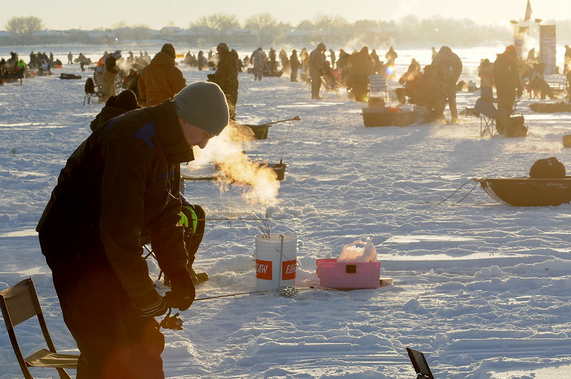 Blowing steam into the below-zero air Saturday morning, Jan. 7, 2017, Denver-area resident Ian Kerns checks his line at the start of the Ice Addiction fishing tournament on Loveland's Boyd Lake. Ian was fishing with his dad, Keith Kerns, and  his uncle, Kevin Kerns.  (Photo by Craig Young / Loveland Reporter-Herald)
