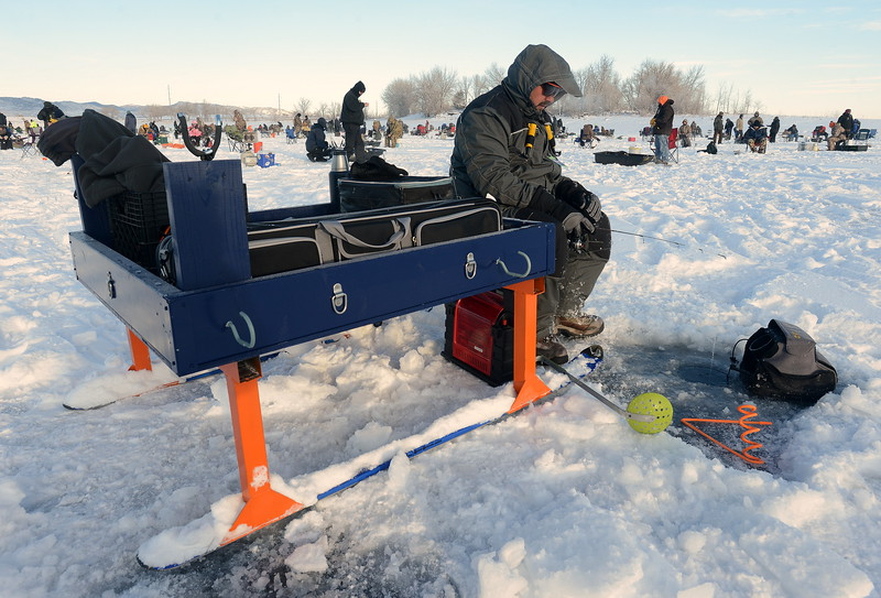 Alonso Montes of Broomfield sits next to the ice-fishing sled he fashioned out of wood and old skis during the Ice Addiction fishing tournament Saturday morning, Jan. 7, 2017, at Loveland's Boyd Lake State Park. Montes said he normally hooks his snow shovel to one side of the rig, his fishing shelter on the other, with his ice auger and other gear on top.  (Photo by Craig Young / Loveland Reporter-Herald)
