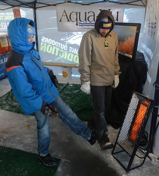 Ten-year-old Angelo Gonzales, left, and his dad, Andrew, warm their feet in front of a heater inside the warming tent at the Ice Addiction fishing tournament Saturday, Jan. 7, 2017, at Boyd Lake in Loveland.  (Photo by Craig Young / Loveland Reporter-Herald)