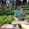 Alex Primeau looks through a pile of free books during the ice cream social at Reingold Elementary School on Tuesday evening. SENTINEL & ENTERPRISE / Ashley Green