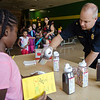 Lt. Jeffrey Howe serves up some sprinkles during the ice cream social at Reingold Elementary School on Tuesday evening. SENTINEL & ENTERPRISE / Ashley Green