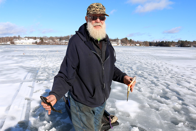 Richard Howell of Fitchburg loves to fish and was out at Lake Whalom on Thursday, like he does just about every day he said, trying to chatch some fish. With the recent warm weather this is one of the only places that the ice was safe enough to go out on. He holds two of the fish he caught Thursday. SENTINEL & ENTERPRISE/JOHN LOVE