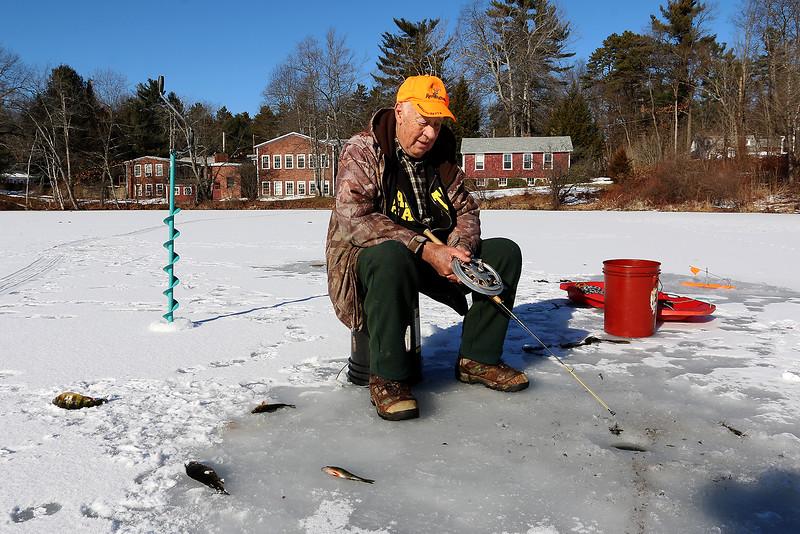 Bill Ferguson Jr., 79, of Lunenburg was enjoying himself ice fishing on the Squannacook River Reservoir just off of Townsend Road in Groton on Friday morning December 23, 2016. SUN/JOHN LOVE