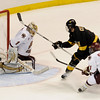 During the 2011 West Regional playoffs at Scottrade Center in St. Louis, Missouri.  Colorado center David Civitarese (11) slips the puck past Boston goalie John Muse (1) for a short handed goal while right winger Steven Whitney (21) back checked.  Colorado College controlled the game as they defeated Boston College 8 to 4 to advance to the West Regional finals.