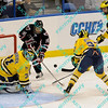 During the 2011 West Regional playoffs at Scottrade Center in St. Louis, MO.  Nebraska-Omaha left winger Johnnie Searfoss (16) sees his stuff attempt get blocked by Michigan goalie Shawn Hunwick (31) while Michigan defenseman Mac Bennett (37) and defenseman Jon Merrill (24) look to clear the rebound.  Michigan defeated Nebraska 3 to 2 with a goal in overtime that had to be determined via a video review to advance to the West Regional finals.