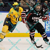 During the 2011 West Regional playoffs at Scottrade Center in St. Louis, MO.  Nebraska-Omaha center Joey Martin (14) skates away from the checking of Michigan left winger Scooter Vaughan (3).  Michigan defeated Nebraska 3 to 2 with a goal in overtime that had to be determined via a video review to advance to the West Regional finals.