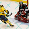 During the 2011 West Regional playoffs at Scottrade Center in St. Louis, MO.  Michigan center Louie Caporusso (29) puts a shot just wide of Nebraska-Omaha goalie John Faulkner (30).  Michigan defeated Nebraska 3 to 2 with a goal in overtime that had to be determined via a video review to advance to the West Regional finals.